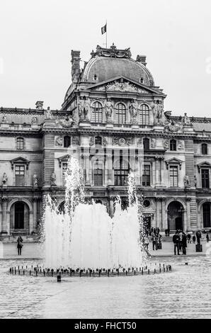 Paris, Frankreich - 17. März 2012: Touristen gehen in der Nähe der Brunnen vor dem Louvre-Museum. Paris, Frankreich - Stockfoto