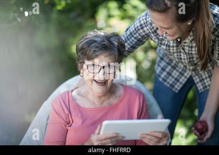 Großmutter und Enkelin im Garten mit digital-Tablette - Stockfoto