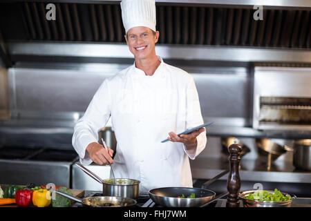 Happy Chef mit TabletPC während des Kochens - Stockfoto