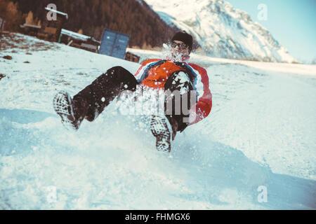 Italien, Val Venosta, Slingia, Mann einen verschneiten Hang hinunter rodeln - Stockfoto