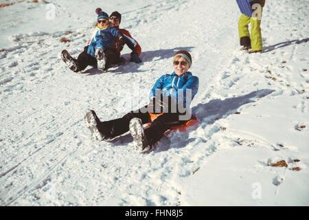 Italien, Val Venosta, Slingia, Familie einen verschneiten Hang hinunter rodeln