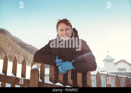 Italien, Val Venosta, Slingia, Porträt von lächelnden reifer Mann am Zaun stehen - Stockfoto
