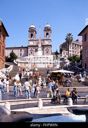Touristen sitzen auf der spanischen Treppe mit einem Brunnen im Vordergrund, Rom, Italien, Europa. - Stockfoto