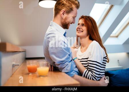 Paar umarmt und trinken Saft in der modernen Küche - Stockfoto
