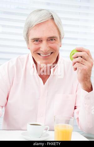 Glücklich Senior mit Apfel und Kaffee am Frühstückstisch - Stockfoto