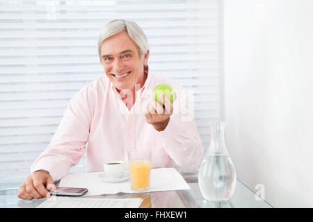Gesunde ältere Mann hält Apfel am Frühstückstisch - Stockfoto