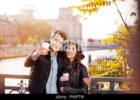 Deutschland, Berlin, junges Paar am Fluss Spree mit Kaffee zum mitnehmen - Stockfoto