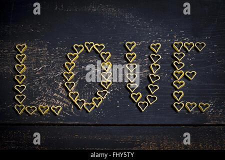 Herzförmige Nudeln bilden die Wotd 'Liebe' auf Holz - Stockfoto