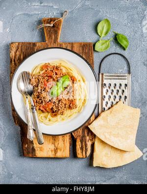 Pasta-Essen. Spaghetti Bolognese in Metallplatte auf rustikalem Holzbrett mit Käsereibe Parmesan und frischem Basilikum - Stockfoto