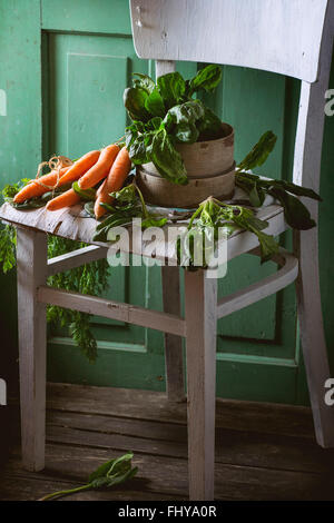 Jede Menge frischer Spinat und Karotten auf alten weißen Holzstuhl mit grünen hölzernen Wand im Hintergrund. - Stockfoto
