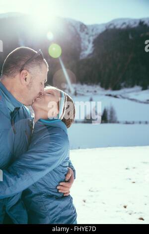 Italien, Val Venosta, Slingia, ältere paar küssen in Winterlandschaft - Stockfoto