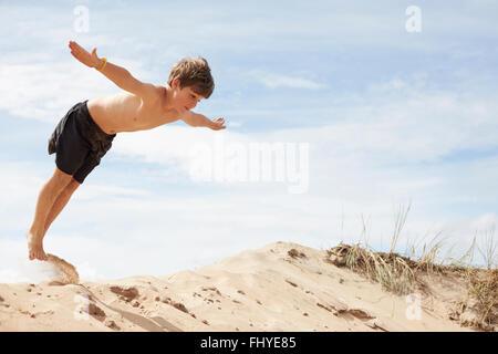 Schweden, Mellby, Boy am Strand Düne mit ausgestreckten Armen in die Luft springen - Stockfoto