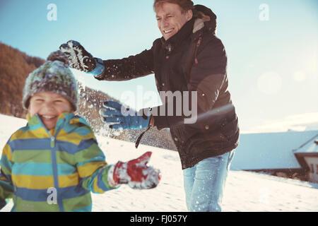 Italien, Val Venosta, Slingia, Vater und Sohn haben eine Schneeballschlacht