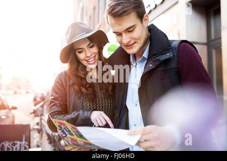 Deutschland, Berlin, junges Paar Stadtplan lesen - Stockfoto