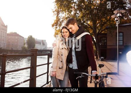 Deutschland, Berlin, junges Paar am Fluss Spree umarmen - Stockfoto
