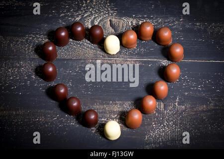 Verschiedene Schokoladen Marshmallows bilden ein Herz auf dunklem Holz - Stockfoto