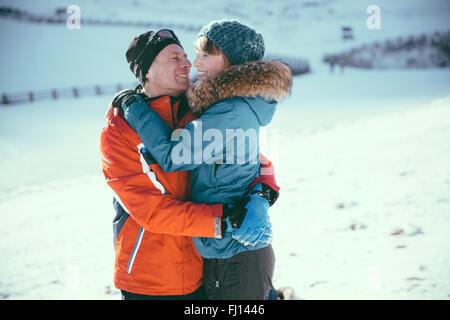 Italien, Val Venosta, Slingia, glückliches Paar umarmt in Winterlandschaft - Stockfoto