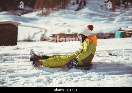Italien, Val Venosta, Slingia, junge einen verschneiten Hang hinunter rodeln - Stockfoto