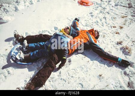 Italien, Val Venosta, Slingia, glücklicher Vater und Sohn im Schnee liegend