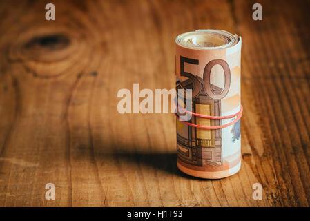 Konzept Geld sparen bares Geld mit Gummiband auf hölzernen Schreibtisch, fünfzig Euro Banknoten persönliche Haushaltsbudget - Stockfoto