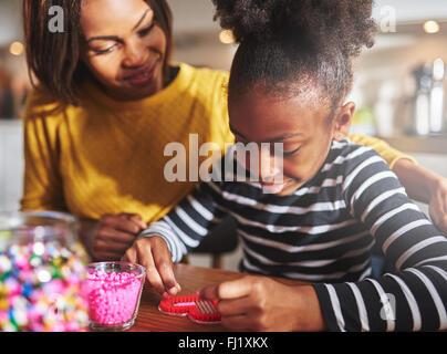 Stolz weiblichen Elternteil, Kind füllen Rahmen in Herzform mit kleinen roten Perlen am Tisch in der Küche mit weichen - Stockfoto