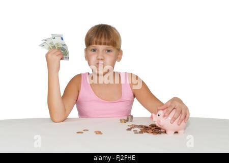 Kleines Mädchen mit Geld in der hand spielen und Sparschwein auf Tisch isoliert - Stockfoto