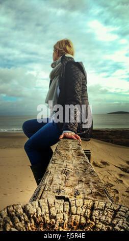junge Frau sitzt auf Holz am Strand