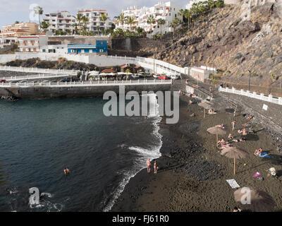 Hafen / Strand in Puerto de Santiago mit schwarzem Lavasand, Urlaubsort an der West Küste von Teneriffa Kanaren - Stockfoto