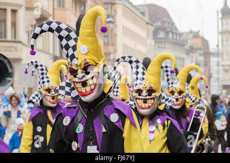 Die Parade der Basler Fasnacht in der Schweiz, mit Clowns, bunten Kostümen, das Konfetti auf die Zuschauer zu werfen. - Stockfoto