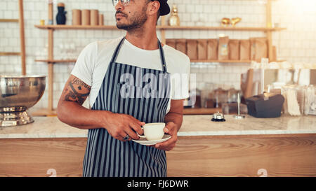 Zugeschnittenen Porträt junger Mann am Café Zähler stehen und wegsehen. Male auf arbeiten in Coffee-Shop. - Stockfoto