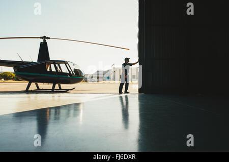 Mechaniker, die Öffnung der Tür von einem Flugzeughangar mit einem Helikopter - Stockfoto