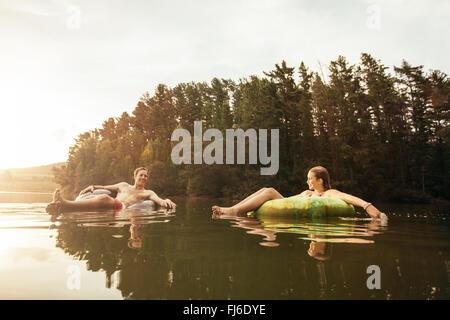 Porträt des jungen Paares im See auf aufblasbaren Ringen. Junges paar entspannende im Wasser an einem Sommertag. - Stockfoto