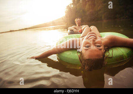 Porträt der glückliche junge Frau mit ihrem Freund im Hintergrund am See in einer Innertube schweben. Junges Paar - Stockfoto