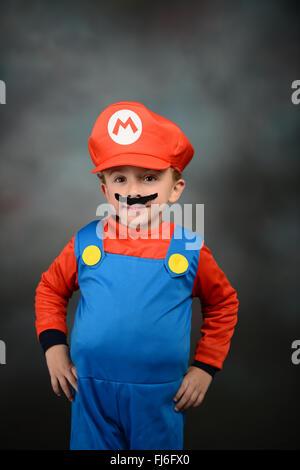 Junge verkleidete sich als Super Mario Bros vor grauem Hintergrund. - Stockfoto