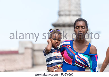 Afro Karibik junge alleinerziehende Mutter mit ihrer kleinen Tochter in die Arme, als sie an einem sonnigen und - Stockfoto