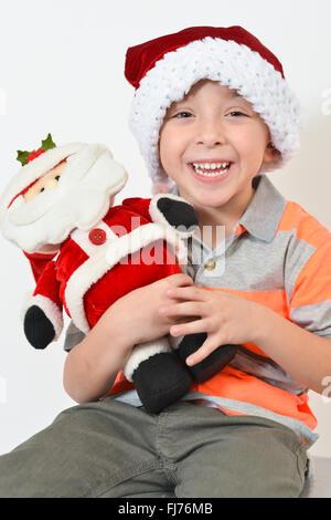 Entzückende junge hält eine Weihnachtsmann Spielzeug während des Tragens einer Weihnachtsmütze - vor weißem Hintergrund. - Stockfoto