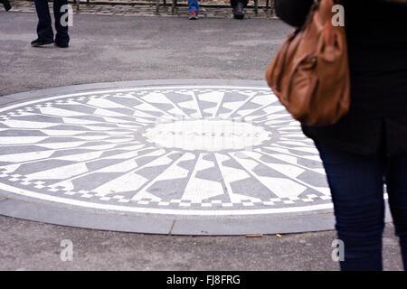 Eine Frau stand auf dem John Lennon vorstellen Denkmal in Strawberry Fields-Abschnitt des New Yorker Central Park - Stockfoto