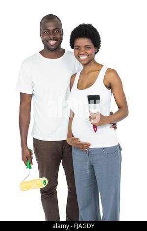 Schwangere paar holding Walze Farbe und Pinsel - Stockfoto