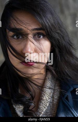 Ernste junge Frau Haar bedeckte Gesicht - Stockfoto