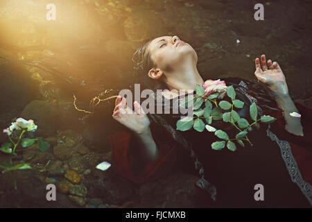 Frau im dunklen Wasser-Strom und weiche Sonnenlicht. Romantik und Tragik Stockfoto
