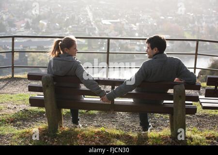 junges Paar sitzt auf der Bank auf der Flussseite, Hände Rheine, Deutschland, hält jede andere - Stockfoto