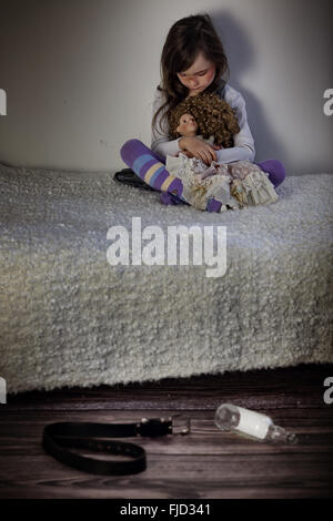 Gewalt in der Familie - verängstigte Mädchen sitzt auf Bett - Stockfoto