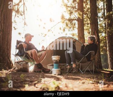 Porträt des reifes Paar sitzen auf Stühlen von Zelt am Campingplatz. Ältere Mann und Frau entspannen und reden in - Stockfoto