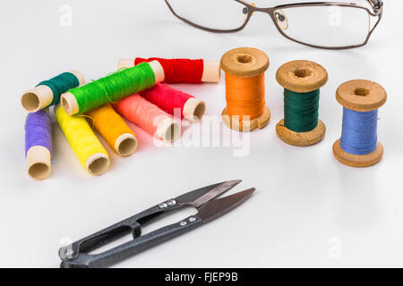 Farbigen Fäden mit einer Schere auf weißem Hintergrund - Stockfoto