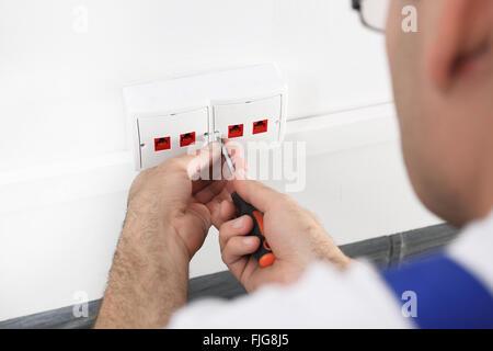 Elektriker. Installation von Internet. Installation von der Steckdose. Man steigt in eine elektrische Steckdose, - Stockfoto