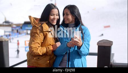 Zwei junge Frauen überprüft eine Telefon Lächeln - Stockfoto