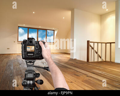 Hände halten eine professionelle Kamera auf Stativ, etwa um einen Schuss eines modernen Interieur mit Holzboden - Stockfoto