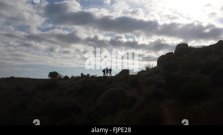 Silhouette von drei Personen auf Hügel - Stockfoto