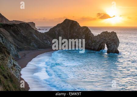 Die aufgehende Sonne an einem Winter Morgen gesehen über dem Kalkstein Bogen von Durdle Door auf Jurassic Küste von Dorset, Großbritannien