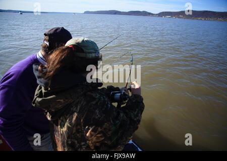 Junges Mädchen Kokons in einen Fisch an der Seite eines Bootes auf dem Hudson River, New York. - Stockfoto